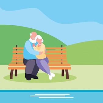 公園の椅子に座っているかわいい老夫婦