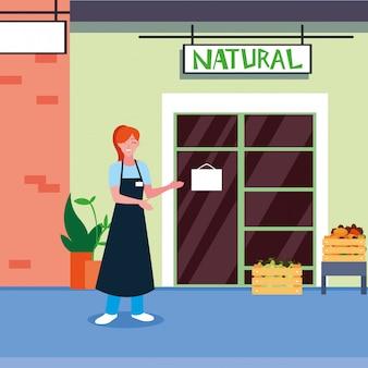 果物の自然な店のファサードを持つ店員