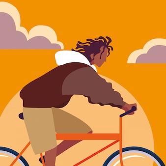 スカイオレンジと若い男アフロ乗馬自転車