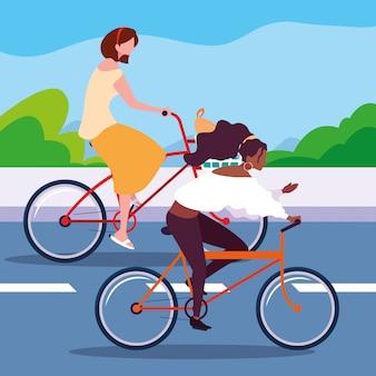 Молодые женщины едут на велосипеде по дороге