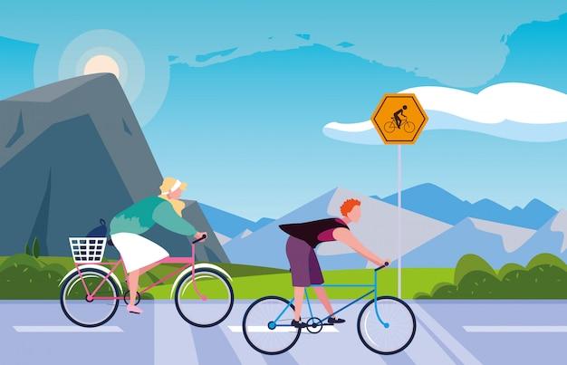 サイクリストのための標識のある風景の中のカップル乗馬自転車