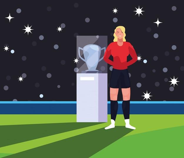 Женщина футболиста на стадионе с трофеем