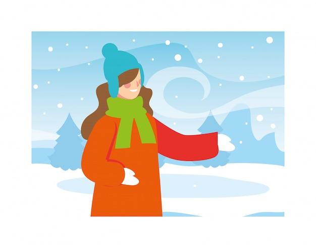 降雪のある風景の中の冬の服の女性