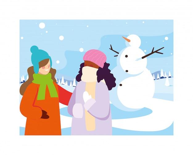 冬の風景の中の雪だるまを持つ女性