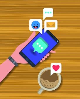 コーヒーカップとソーシャルアイコン付きのスマートフォンを使用して手を