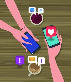 スマートフォンでコーヒーカップやソーシャルアイコンを使用している人