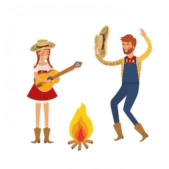 Пара фермеров танцует с соломенной шляпой и костром