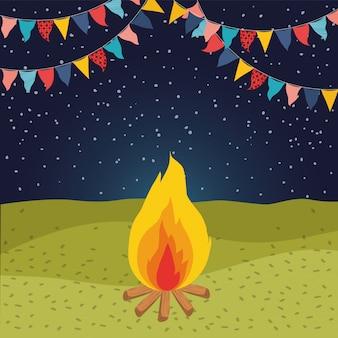 キャンプファイヤーと花輪の夜景のあるフィールド