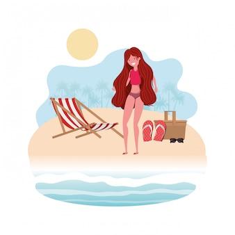 ピクニックバスケットが付いている浜の海岸の女性