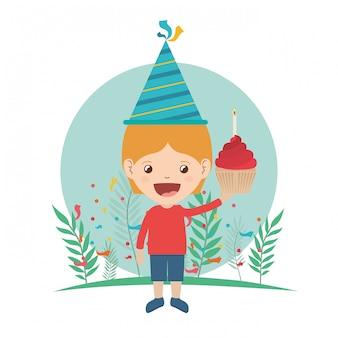 パーティの帽子と誕生日のお祝いのケーキを持つ少年