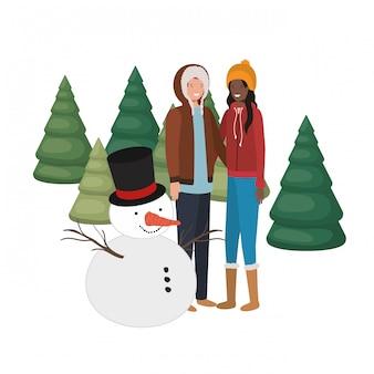 カップルは雪だるまと松の木