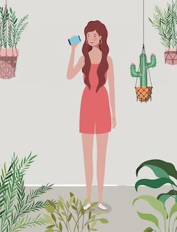 スマートフォンで庭の若くて美しい女の子