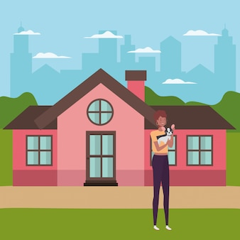 Молодая женщина, лифтинг милая собака в доме на открытом воздухе