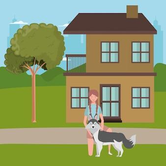 家の屋外のかわいい犬を持つ若い女性