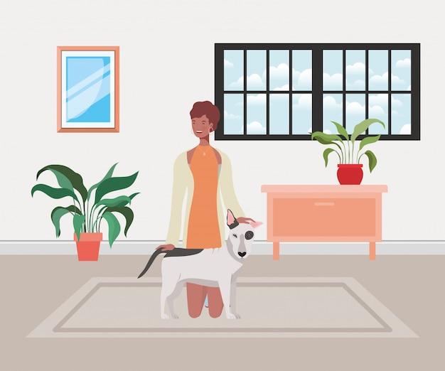 家の部屋でかわいい犬を持つ若い女性
