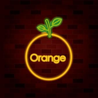 レンガの壁のオレンジ色の果物とネオンサインのテキスト