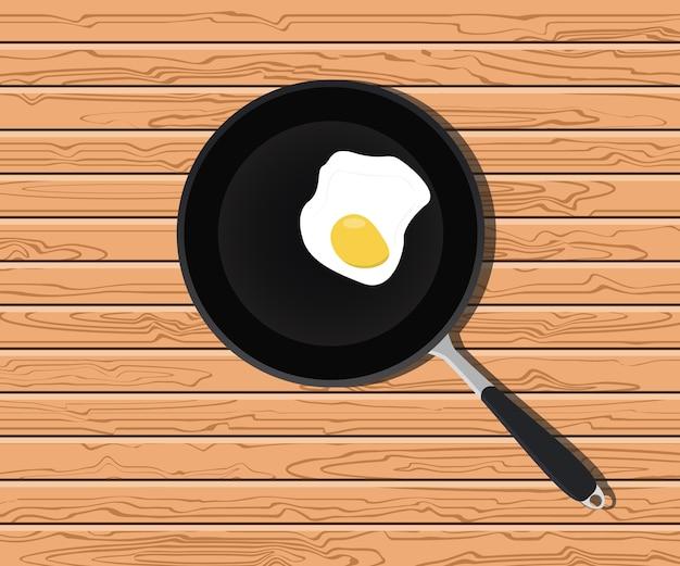 フライパン、木製のテーブルで卵