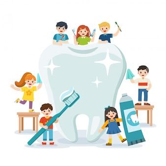 Группа в составе усмехаясь мальчики и девочки стоя рядом с большим белым зубом держа зубную щетку показывая здоровый чистый зуб ободряя гигиену и заботу зубов.