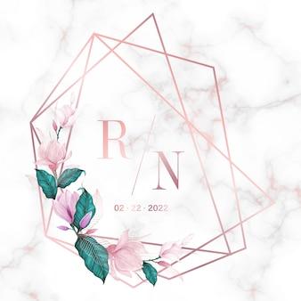 結婚式のモノグラムのロゴと招待状カードの大理石の背景に花とローズゴールドの幾何学的なフレーム