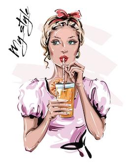 手描きのドリンクを飲みながら美しい若い女性。ヘッドアクセサリーとスタイリッシュなピンナップガール。ファッション女性を見てください。
