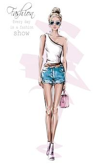 手描きのサングラスで美しい若い女性。ファッション女性の服。ジーンズのショートパンツでスタイリッシュな女の子。ファッション女性を見てください。