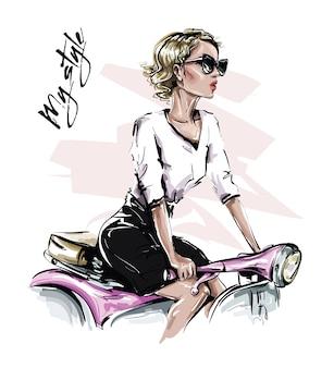 手描きのサングラスで美しい若い女性。自転車に座っているスタイリッシュな女の子。ファッション女性を見てください。