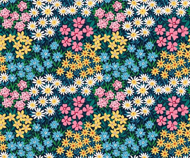 暗い青色の背景に小さなカラフルな花と花のパターン。頭が変なスタイル。ヴィンテージの花の背景。デザインとファッションのプリントのシームレスパターン。