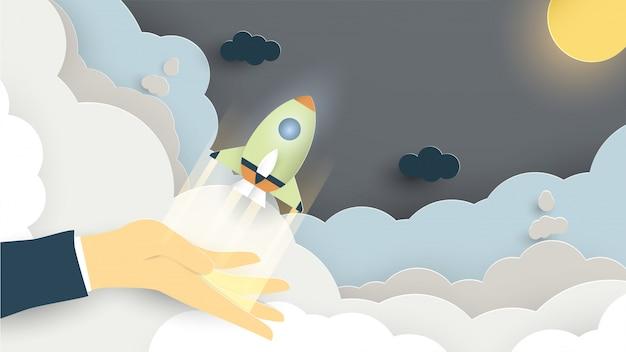 紙のカット、クラフト、折り紙のスタイルでコンセプトを起動のイラスト。ロケットが飛んでいます。