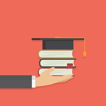 卒業生の帽子と本のスタックを持っている手