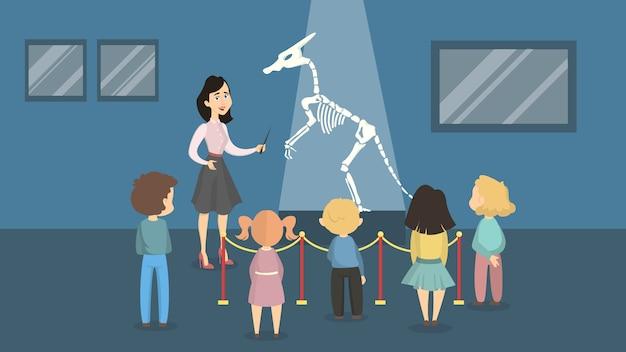 恐竜の骨格を見ている歴史博物館の子供たち。女性ガイド。