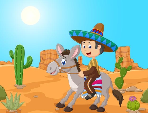砂漠の背景でロバを運転しているメキシコの男性