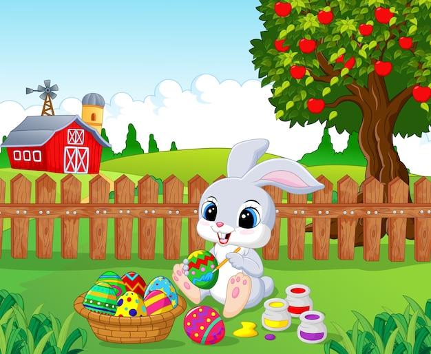 かわいいイースターバニー、卵を庭に描く