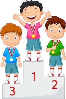 小さな男の子が表彰台で彼の金メダルを祝う