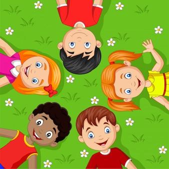 草の上に横たわる漫画の子供たち
