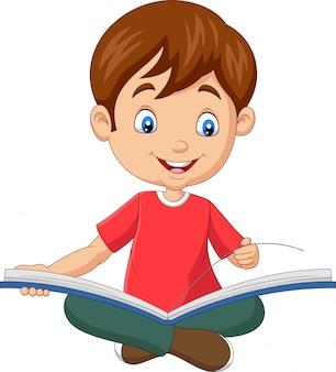 座っている幸せな少年は本を開いた
