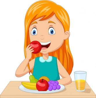 テーブルで果物を食べる少女