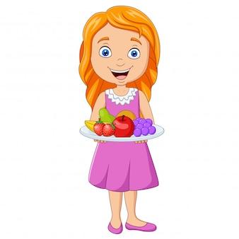 新鮮な果物の皿を持って少女