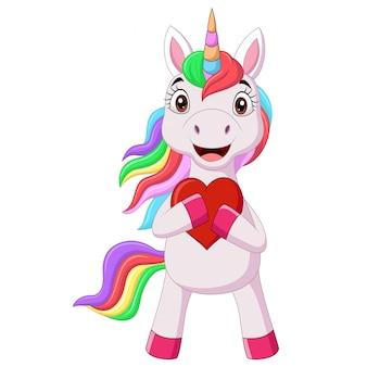 Милый маленький пони единорог держит красное сердце