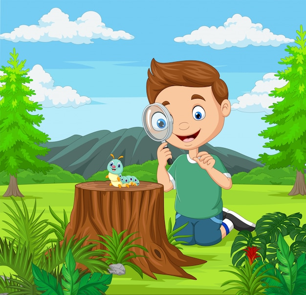 Маленький мальчик, глядя на гусеницу, используя лупу в саду