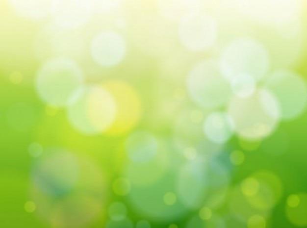 緑のピンぼけ自然光沢のある背景