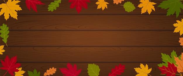 メープルの葉で飾られた木の板に秋のバナーヘッダーの背景を飾る