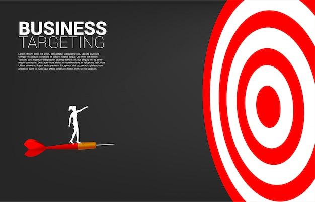 Силуэт бизнесвумен, стоя на стрелке стрелка указывает вперед, чтобы дартс.