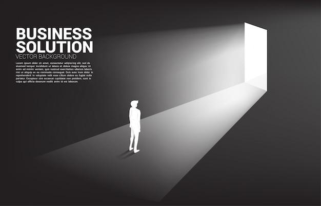 出口のドアの前に立っている実業家のシルエット。キャリアアップのコンセプトとビジネスソリューション。