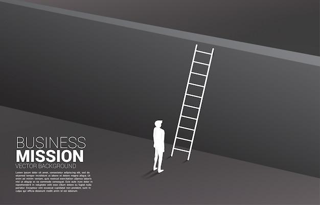 はしごで壁を横断する準備ができているビジネスマンのシルエット。ビジョンミッションのコンセプトとビジネスの目標