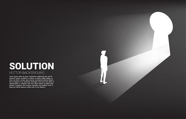 Силуэт бизнесмена готов выйти вне к отверстию для ключа. найти концепцию концепции видение миссии и цели бизнеса
