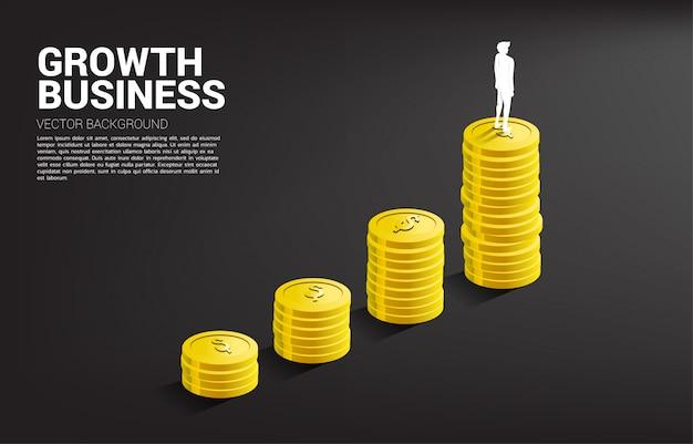 コインのスタックで成長グラフの上に立っている実業家のシルエット。