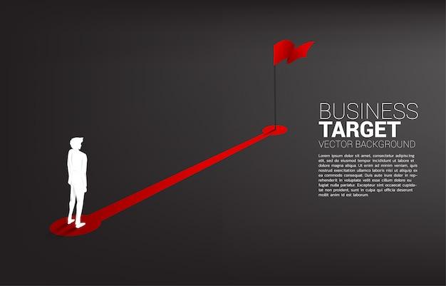 目標の背景に赤い旗へのルートパス上に立っている実業家のシルエット