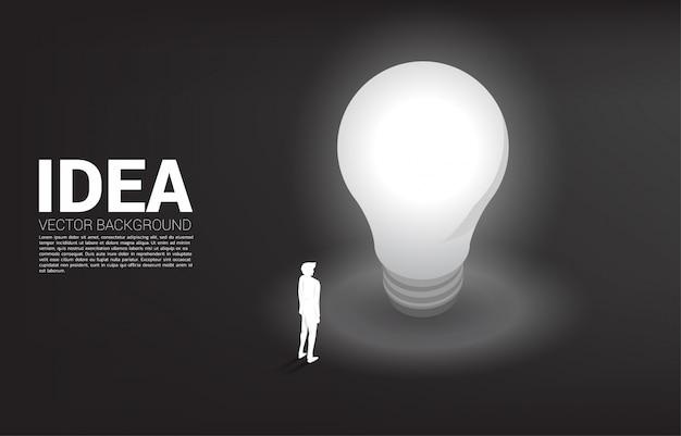 電球で立っている実業家のシルエット。