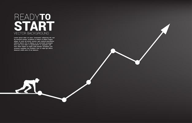 Силуэт бизнесмена готового для запуска от линии старта на растущей диаграмме.