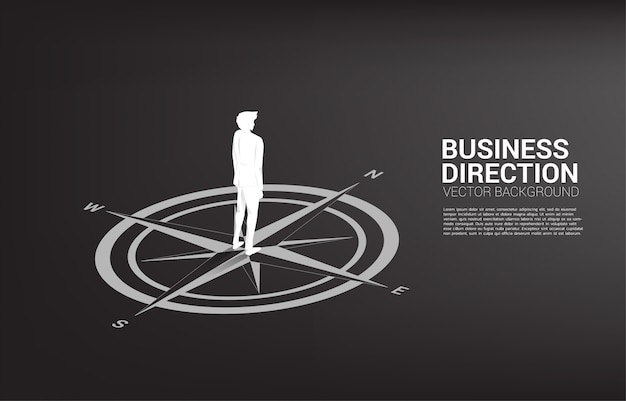 床のコンパスの中心に立っている実業家のシルエット。キャリアパスとビジネスの方向性